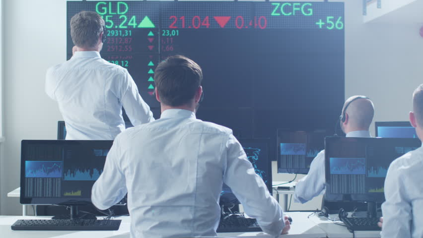 Group of Stockbrockers Actively Working using Headsets and Phones at Stock Exchange. Shot on RED Cinema Camera in 4K (UHD).