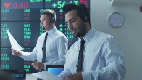 Hispanic Ethnicity Stockbroker is Actively Talking using Headset at Stock Exchange. Shot on RED Cinema Camera in 4K (UHD).