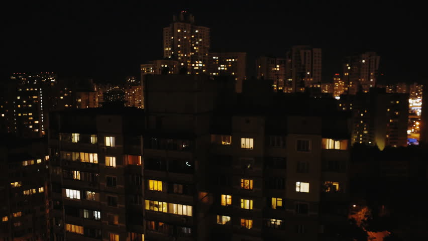 Windows and roof of a multistory house at night....