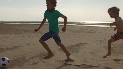 boys kicking soccer ball at beach, kids playing football slow motion