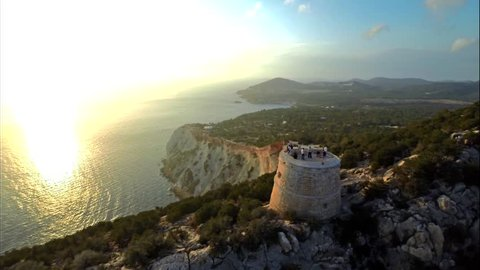 Aerial view of an old tower named Torre del Pirata, on the top of a cliff, in front of an islet named Es Vedra, at sunset, in the island of Ibiza.