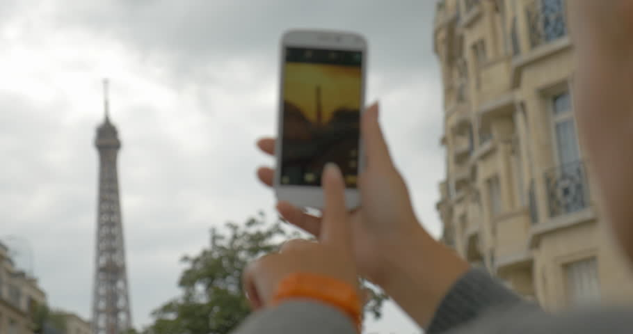 Woman tourist with smart phone making Eiffel Tower shots in retro style and then zooming and looking at photo. Sightseeing of Paris, France