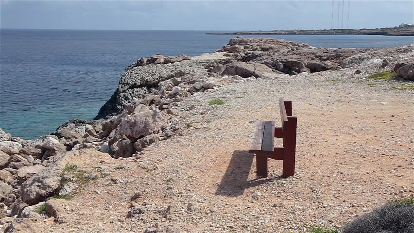 Lonely wooden bench on the rocky coast of the island of Cyprus. Cape Cavo Greco. Cyprus