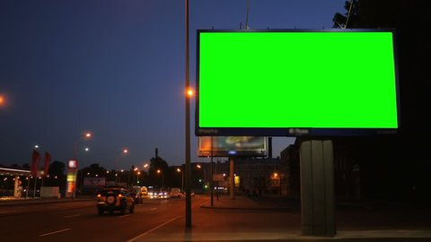 A Billboard with a Green Screen on a Busy Night Street