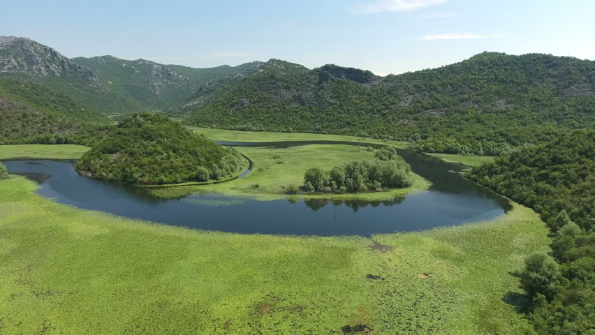 Camera flying over watercourse bend of Rjieka Crnojevica. Beauty nature with green plants on water surface. Part of Skadar lake and national park in Montenegro | Shutterstock HD Video #17813500