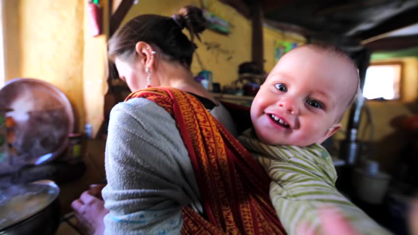 5bd65bfc810 Mother is carrying her son on her back in sling so her arms are free for  cooking. The boy is smiling and trying to touch the camera. Chachzaevka  Ecovillage.
