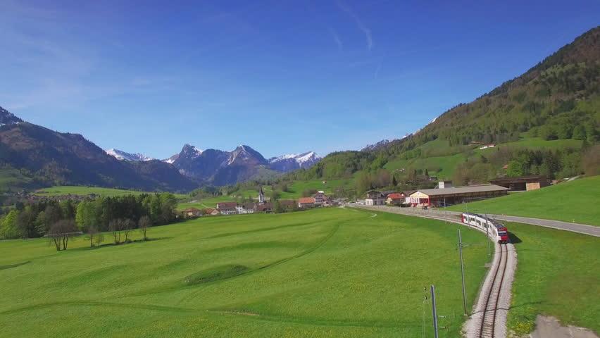4K Swiss train aerial shot / Following a commuter train in the countryside - idyllic mountain landscape Switzerland