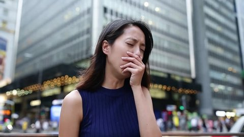 Woman coughing outside due to air pollution