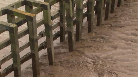 Close up of brown silted river bank with wooden posts next to the river Humber in Hull, UK