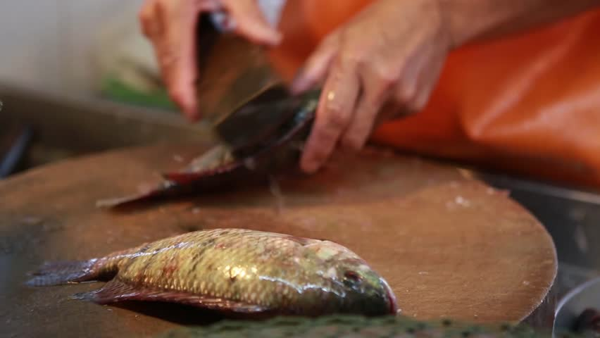 Local fish vendor scales and cleans a tilapia