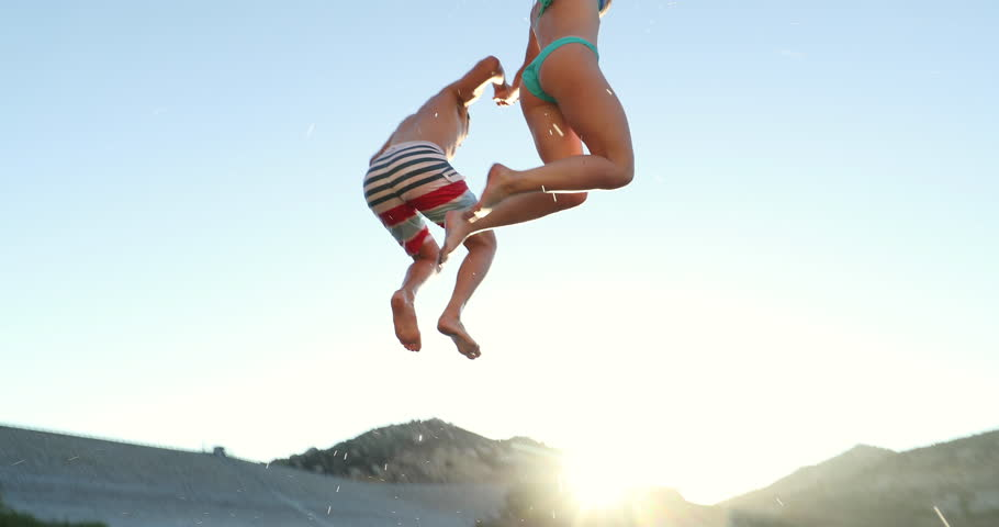 Young Adult Couple Holding Hands Jumping Into Lake In Slow Motion