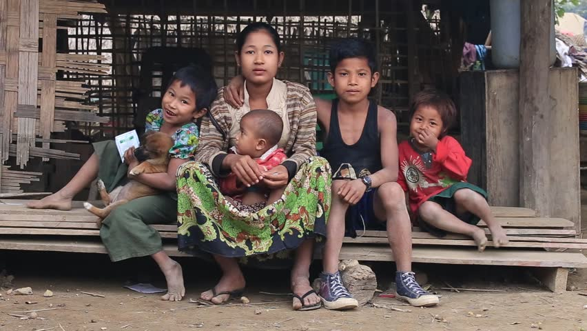 MRAUK-U, MYANMAR - JANUARY 28, 2016: Unidentified poor family sits on the street. Poverty is a major issue in Burma