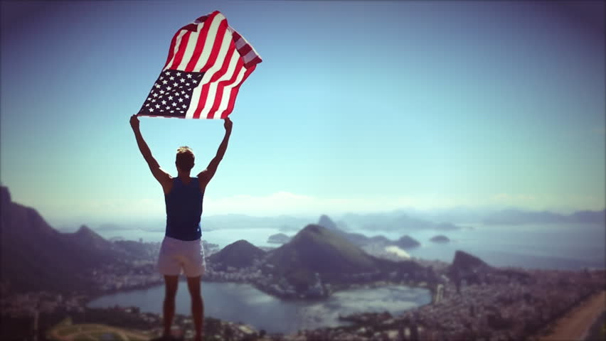 Athlete stands holding an American flag waving in slow motion at a bright overlook of the city skyline of Rio de Janeiro, Brazil #18005950