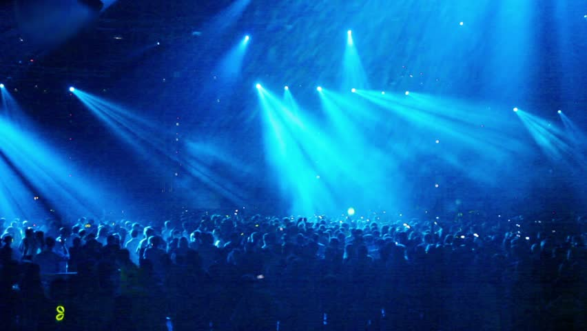 Crowd at rave party, people dance in blue light of projectors