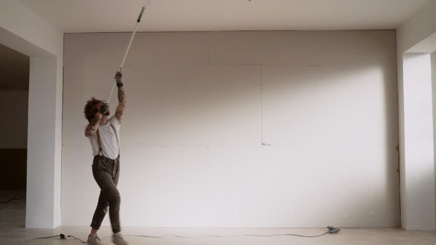 Funny curly man wears pants with suspenders acts like he is dancing waltz while painting celling with brush roller and white paint Home diy renovation | Shutterstock HD Video #18026470
