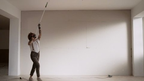 Funny curly man wears pants with suspenders acts like he is dancing waltz while painting celling with brush roller and white paint Home diy renovation