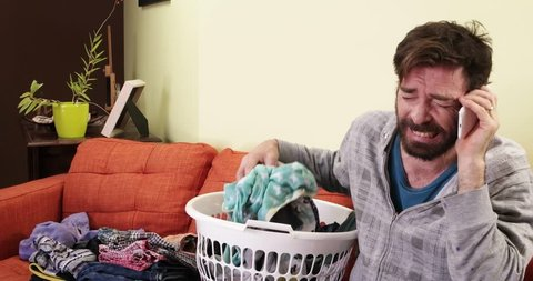 man folding laundry being angry on phone