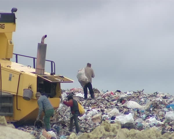 Poverty. Dump. Special machine pressing rubbish and homeless people looking for items and food. Environmental pollution.