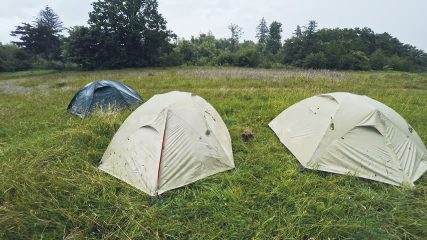 Three tents standing on the lawn in the rain. Wide angle. - 4K stock & Grey Tent On A Campsite In The Rain With Car Parked Stock Footage ...