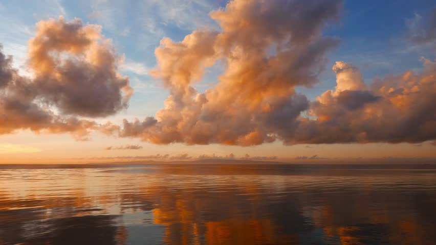 A Dumaguete sunrise video with fiery clouds over the calm ocean. Clouds change color as the sun rises. Presented as time lapse and shot in 4K (Ultra HD) resolution.
