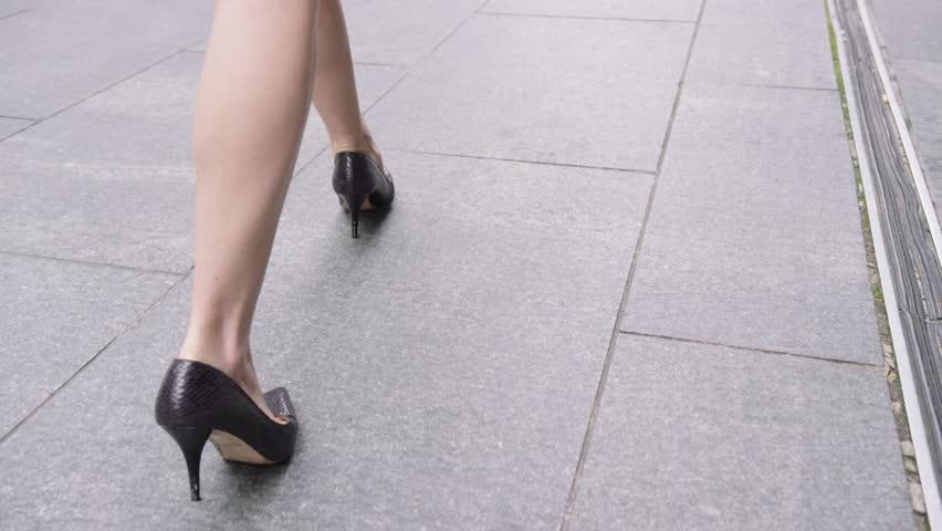 legs black high heels walking in city