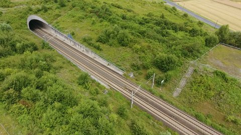Aerial view of a railroad track and tunnel - passing train