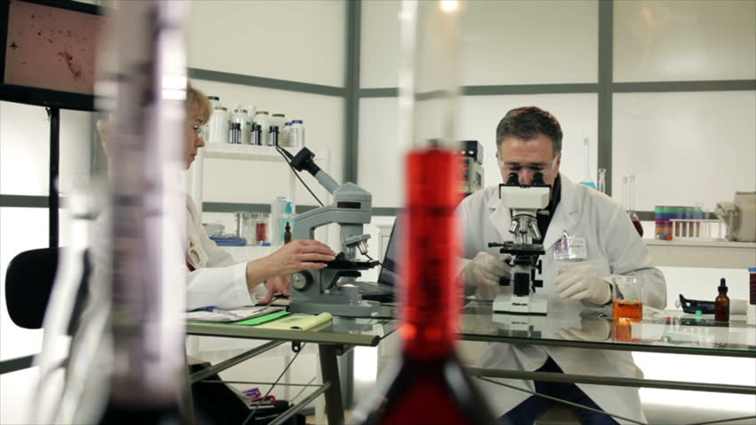 A woman and man who appear to be scientists or chemists working in a laboratory using microscopes and discussing findings. Slow dolly movement past colorful objects in the foreground.