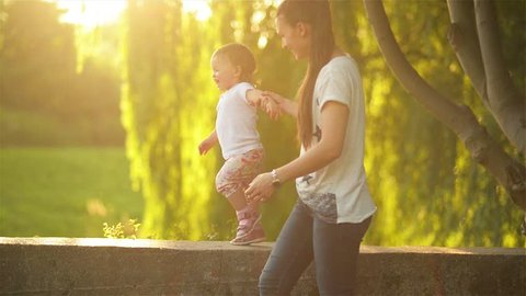 Mother and daughter walking in nature, beautiful mom with her little children running in the park on a warm summer day