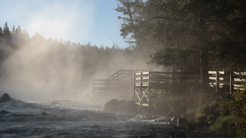 Yellowstone River with mist drifting near boardwalk overlook. Blue water, white mist and dark forest. Sunshine shining through with rays. Romantic and peaceful with a hint of mystery.