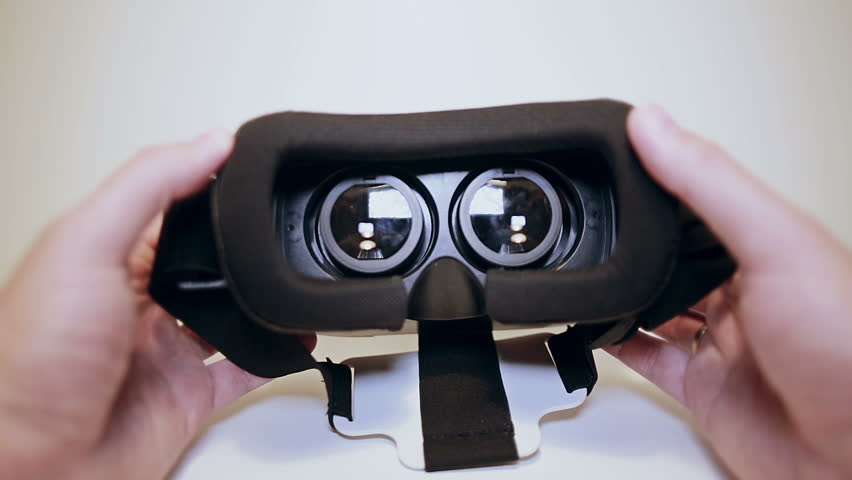 Mans hands take virtual reality glasses, vr and wear them, white background