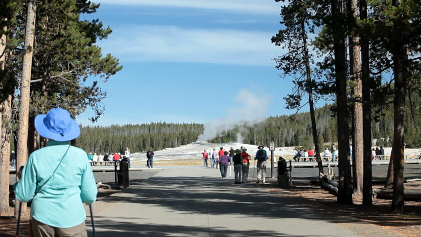 Spectators visit Old Faithful Geyser Yellowstone National Park, Wyoming. Most famous geyser in the world.