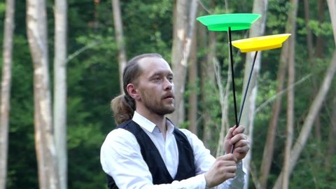 Circus Performer Stands on Stilts and Rotates the Plate Juggling. the Action in Slow Motion.