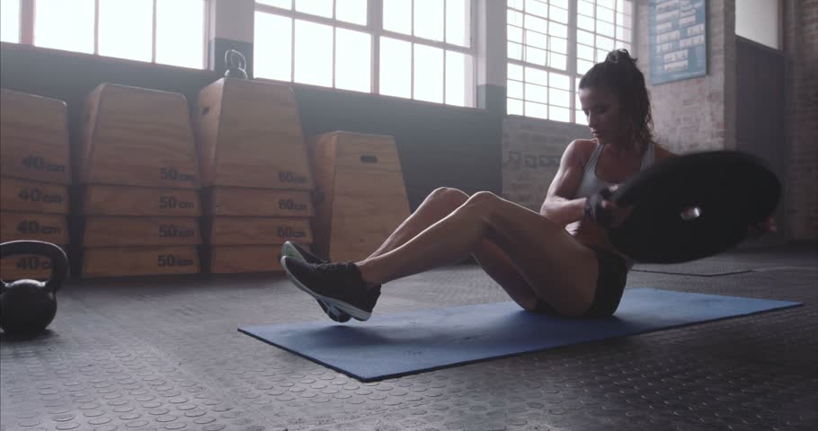 Muscular woman exercising with a weight plate. Fitness woman working out on core muscles at cross fit gym. Weight plate torso twist on exercise mat.