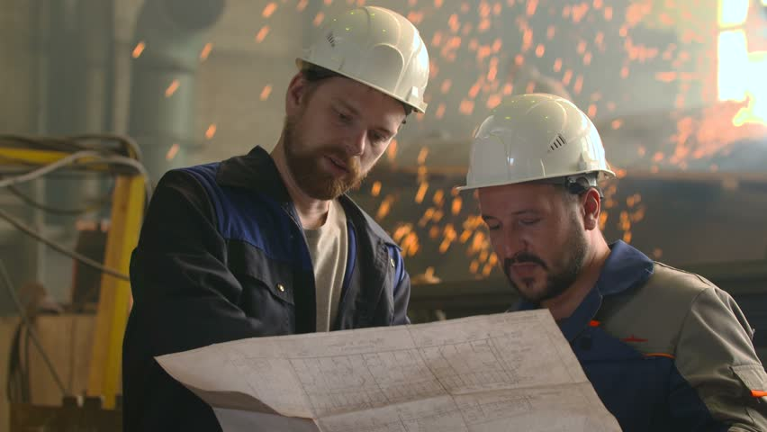 portrait of two engineers explore and discuss project in heavy industry factory. welding background