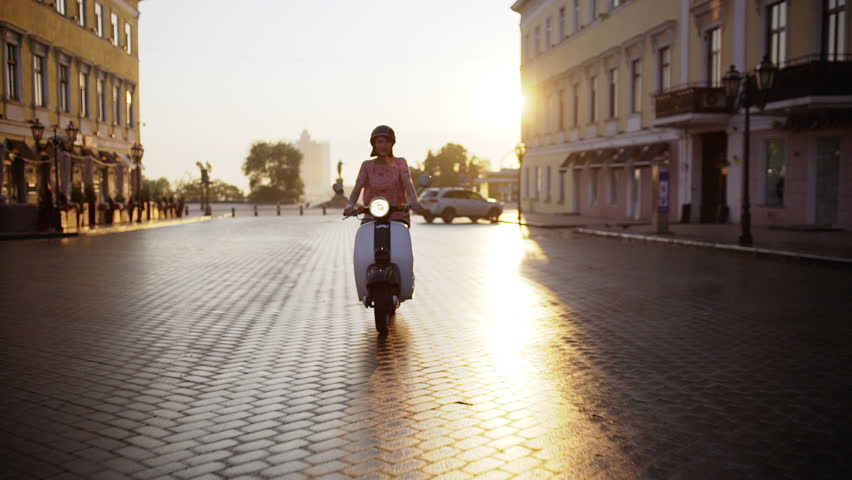 Young beautiful girl riding around city on scooter at sunrise. Slow motion.