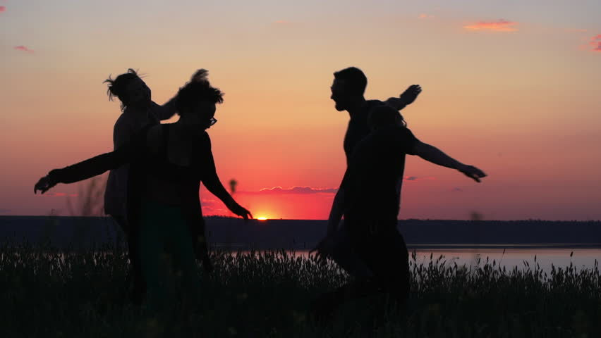 Silhouettes of young people have fun at sunset. Slow motion.