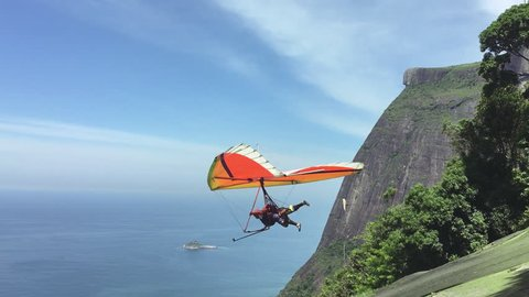 RIO DE JANEIRO - MARCH 22, 2016: A hang glider launches in slow motion from the mountain ramp at Pedra Bonita, in the Tijuca National Forest above Sao Conrado beach.