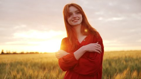 Young beautiful girl with foxy hair in red dress walking in field. Slow motion.