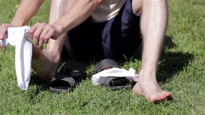 dress socks and white sandals/a man wearing white socks sitting on the grass and put on sandals