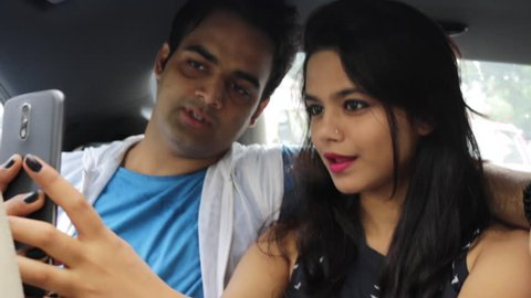Young Indian Couple inside car.