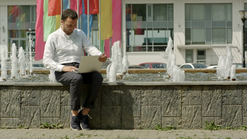 Business man with laptop outside on a bench next to fountain working | Shutterstock HD Video #18227590