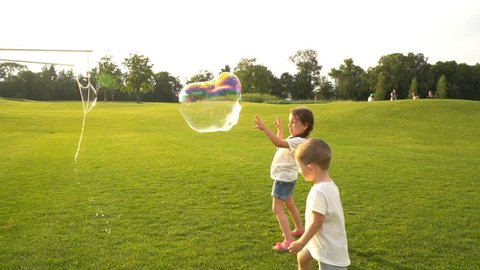 Girl and boy together chasing big soap bubbles. Cheerful summer games in nature. Active leisure  days. Slow motion video footage.  Contre-jour Backlight.  Flares flecks of sunlight