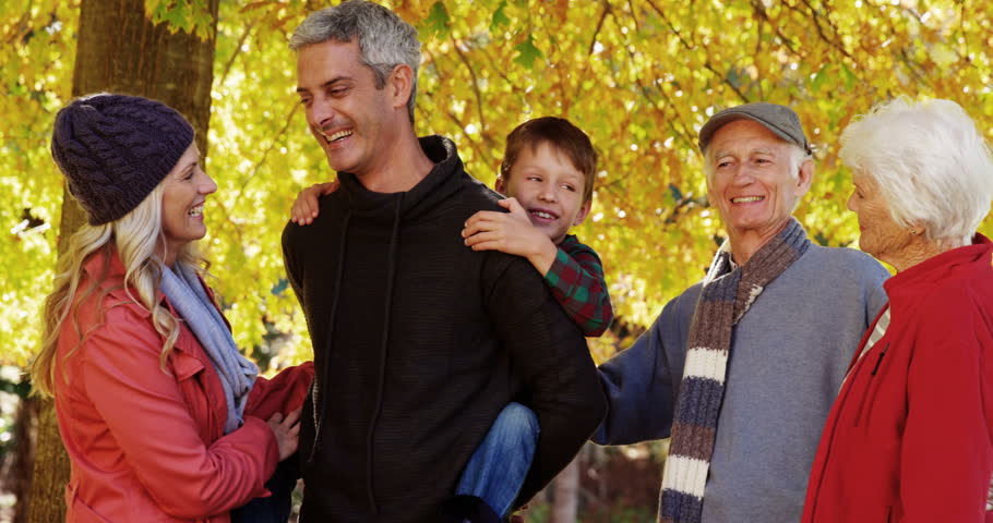 Boy on a dad back with family standing next outdoors | Shutterstock HD Video #18237850