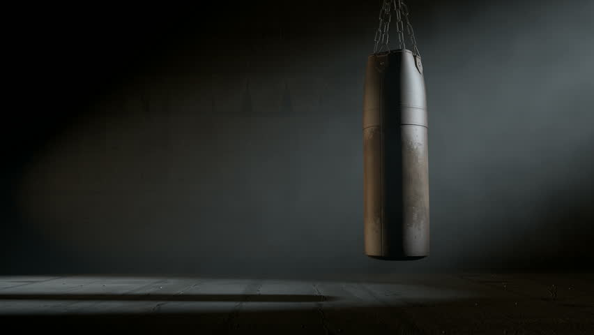 An animated  3D render of an old worn vintage leather punching bag swaying slightly in a room dark room lit by an ethereal spotlight