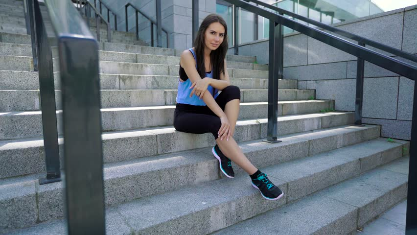 Female urban athlete sitting on stairs after outdoor workout. Sporty woman wearing fashion sport black leggings and blue shirt #18280390