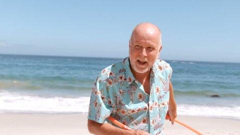 an elderly man doing hula hoop on the beach