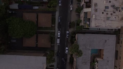 Bird's eye view aerial shot of urban residential street - Professional drone souring threw the air tilting up from street with cars, towards the sunset lit hills w/ residential buildings during dusk