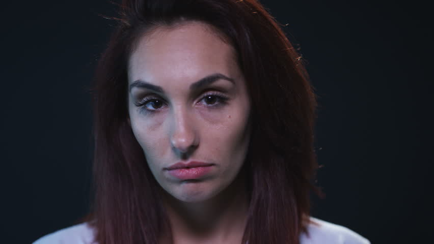 Sad young woman looking at camera on black background | Shutterstock HD Video #18390010