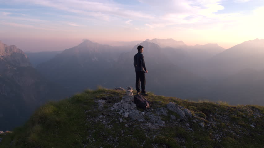 Aerial - Flying from front to behind the man standing on top of the mountain watching beautiful sunset over the peaks #18395320