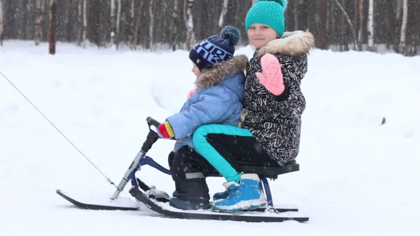 Happy boy and girl ride on sled and wave hands during snowfall in park